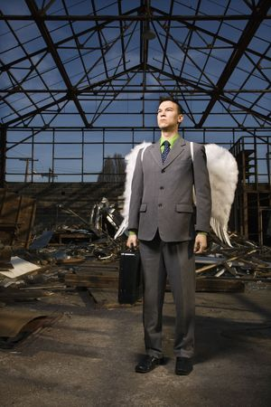 Seus young businessman wearing angel wings holds a briefcase inside an abandoned building. Vertical shot. Stock Photo - 6455393