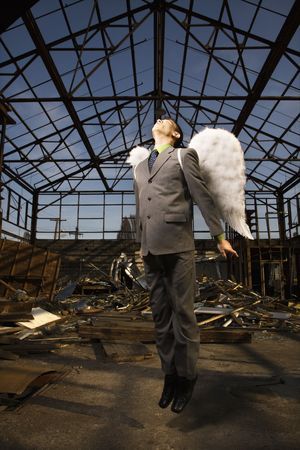 Young businessman with angel wings attempts flight in an abandoned building. Vertical shot.