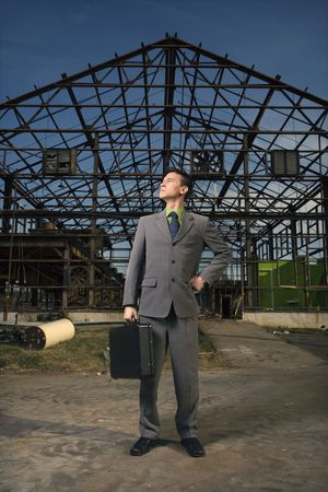 Young businessman stands confidently with a black briefcase in one hand and other hand on his hip. Vertical shot. Stock Photo - 6455414