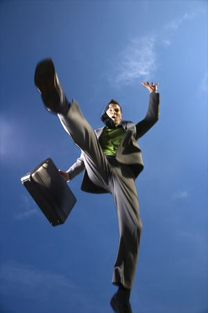 Young businessman leaps over the viewer with a briefcase in hand. Vertical shot.