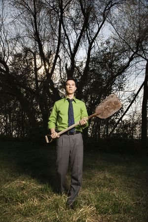 Young businessman standing near the woods with a shovel in hand. Vertical shot. photo