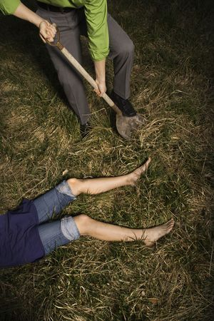 Businessman digs into the ground with a shovel to bury a womans body. Vertical shot. photo