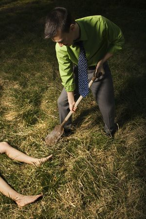 dug: Young businessman uses a shovel to bury a womans body out in a field. Vertical shot.