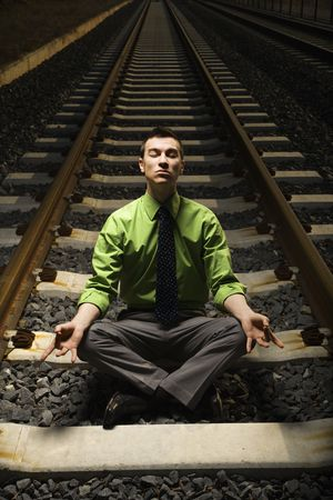 Young businessman sits in a lotus position and meditates while on railroad tracks. Vertical shot. photo