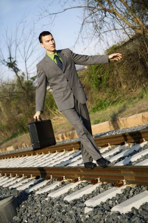 Young businessman with briefcase walks and balances on railroad tracks. Vertical shot. photo