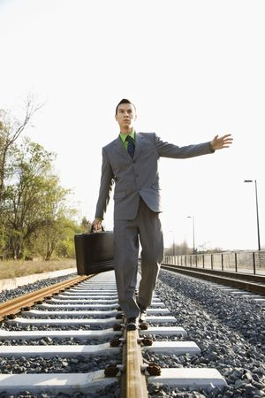 Young businessman with a briefcase balances on railroad tracks. Vertical shot. photo