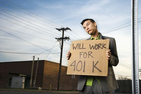 Young businessman stands on a street corner holding a sign that reads will work for 401 K. Horizontal shot.