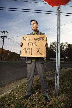 Young businessman stands on a street corner, holding a sign that reads will work for 401 K. Vertical shot. photo