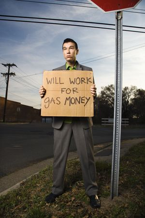 Young businessman stands on a street corner holding a sign that reads will work for gas money. Vertical shot. photo