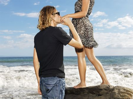 Woman stands on a rock by the ocean while a handsome young man kissing her hand. Horizontal shot. photo