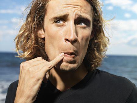 dedo me�ique: Apuesto joven tiene su dedo me�ique hasta su desembocadura y hace una divertida expresi�n facial en la playa. Horizontal a tiros.