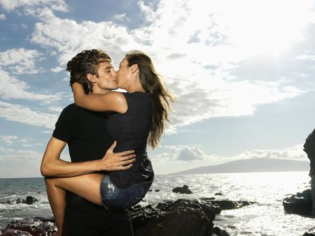 Attractive young couple in a passionate embrace and kissing on a rocky coast. Horizontal shot. Stock Photo - 6421049