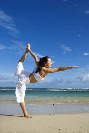 Side view of an Asian woman in a Yoga pose on Maui Hawaii beach with the ocean in the background. Vertical shot.