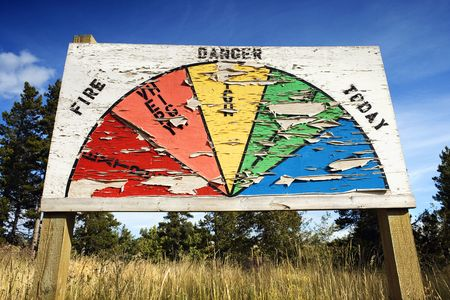 charting: Low angle view of weathered sign charting the level of fire danger. Horizontal shot.