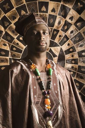 Portrait of an African American man wearing traditional African clothing, in front of a patterned wall and looking at the camera. Vertical format. Standard-Bild