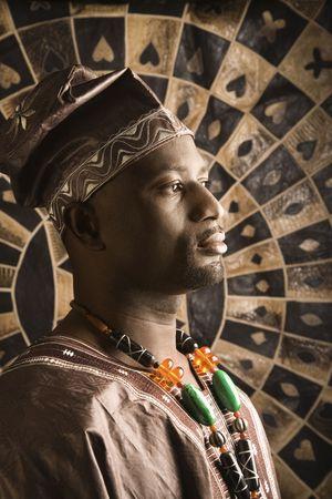 Profil-Porträt eines afroamerikanische Mannes tragen traditionelle afrikanische Kleidung, vor der einer gemusterten Wand. Vertikale Format.