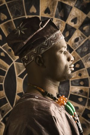 Profile portrait of an African American man wearing traditional African clothing, in front of a patterned wall. Vertical format. Stock Photo - 6497198