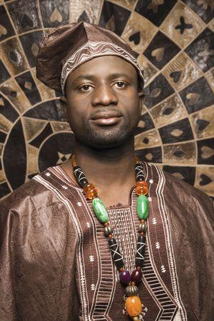 Porträt eines afroamerikanische Mannes tragen traditionelle Afrikanisch Kleidung, vor der einer gemusterten Wand und Blick auf die Kamera. Vertikale Format.