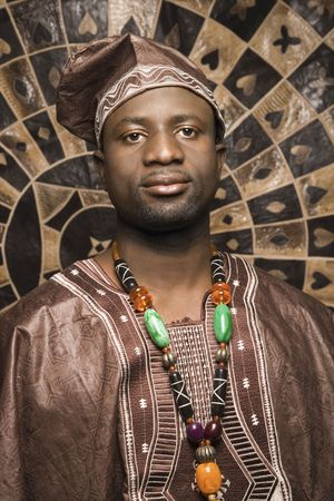 Portrait of an African American man wearing traditional African clothing, in front of a patterned wall and looking at the camera. Vertical format. Stock Photo