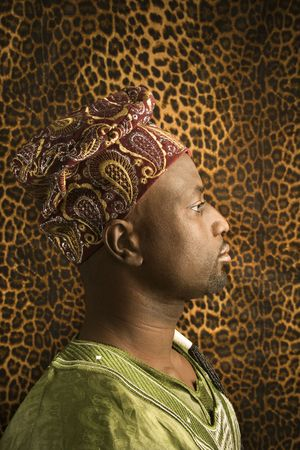 Profile portrait of an African American man wearing traditional African clothing, in front of a patterned wall. Vertical format.