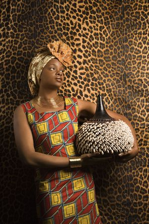 shekere: Portrait of an African American woman wearing traditional African clothing and holding a shekere in front of a patterned wall. Vertical format.