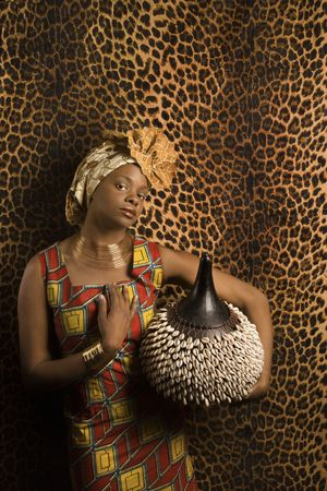Portrait of an African American woman wearing traditional African clothing and holding a shekere in front of a patterned wall. Vertical format.