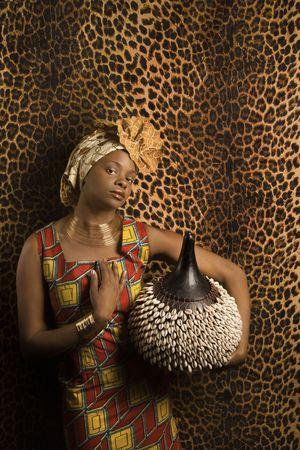 mujeres africanas: Retrato de una mujer afroamericana, vistiendo ropa africana tradicional y sosteniendo un shekere delante de una pared con patr�n. Formato vertical.