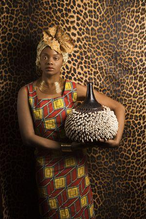 Portrait einer afroamerikanische Frau tragen traditionelle afrikanische Kleidung und halten eine Shekere vor der einer gemusterten Wand. Vertikale Format.