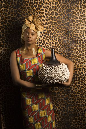 Portrait of an African American woman wearing traditional African clothing and holding a shekere in front of a patterned wall. Vertical format. Stock Photo - 6497204