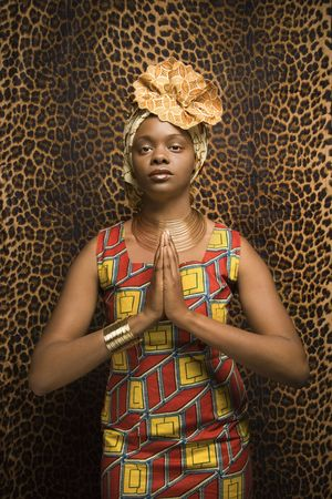 Portrait of an African American woman wearing traditional African clothing in front of a patterned wall and holding her hands in a prayer position. Vertical format. Stock Photo - 6497201