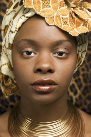 african woman face: Close-up portrait of an African American woman wearing traditional African clothing in front of a patterned wall. Vertical format. Stock Photo