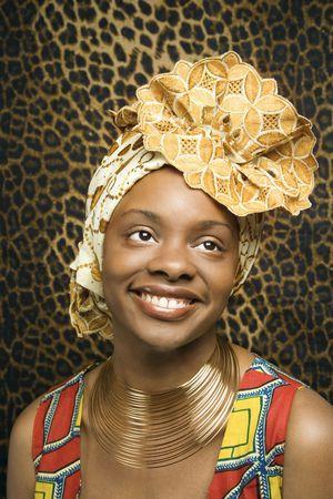 head-dress: Portret powiÄ uśmiech amerykańskiego kobieta ma na sobie tradycyjne odzież afrykańskiego z przodu z deseniem ściany. Format pionowe.