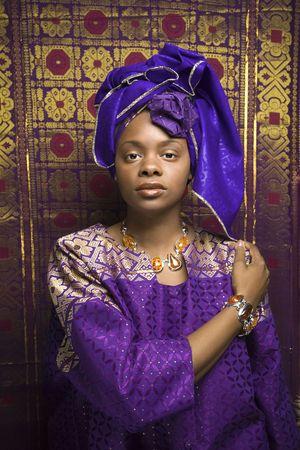 Portrait einer afroamerikanische Frau tragen traditionelle afrikanische Kleidung vor der einer gemusterten Wand. Vertikale Format. Lizenzfreie Bilder