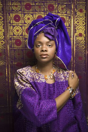 Portrait of an African American woman wearing traditional African clothing in front of a patterned wall. Vertical format. Stock Photo