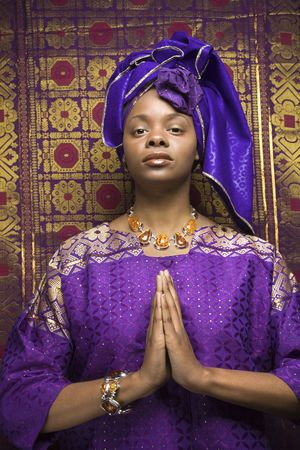 purple dress: Portrait of an African American woman wearing traditional African clothing in front of a patterned wall and holding her hands in a prayer position. Vertical format.