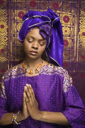 Portrait of an African American woman wearing traditional African clothing in front of a patterned wall and holding her hands in a prayer position. Vertical format.