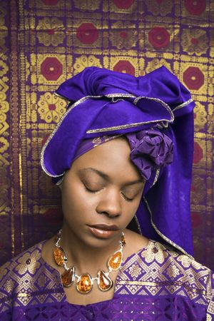 Portrait of an African American woman wearing traditional African clothing and closing her eyes in front of a patterned wall. Vertical format.
