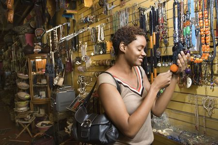 Smiling African American woman standing and looking at a retail display of necklaces. Horizontal format. Stock Photo