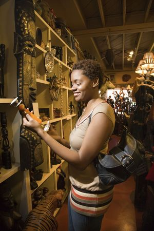 Lächelnd afroamerikanische Frau, stehend und Blick auf einer Kerze oder Vase in einer Retail-Anzeige. Vertikale Format.