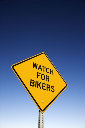 Watch for Bikers road warning sign and blue sky. Vertical shot. photo
