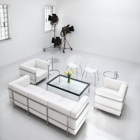 home lighting: White living room furniture in a white photography studio with commercial lighting in the corner. Square format.