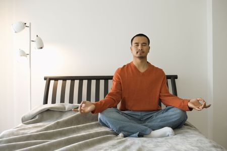 Young man sitting on bed in the lotus position. Horizontal shot. Stock Photo - 6424798