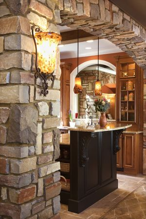 sconce: Stone archway framing dark wood cabinet with marble counter top in luxury home. Vertical shot.