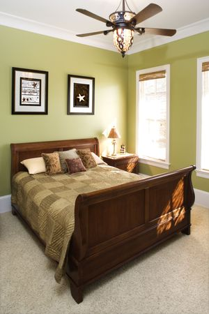 Sleigh bed in a green bedroom with a ceiling fan and wall art. Vertical shot.