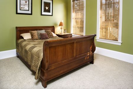 Sleigh bed in a green bedroom with wall art. Horizontal shot.