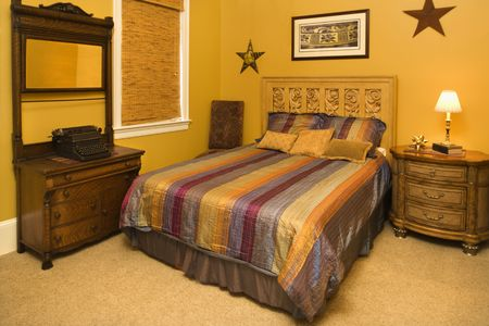 bedspread: Bed with striped bedspread and dresser in the bedroom of an affluent home. Horizontal shot. Stock Photo