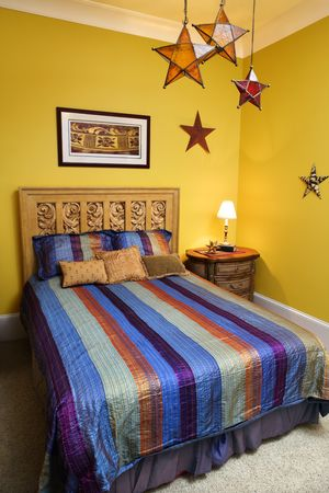 bedspread: Bed with striped bedspread, decorative stars, and nightstand. Vertical shot. Stock Photo
