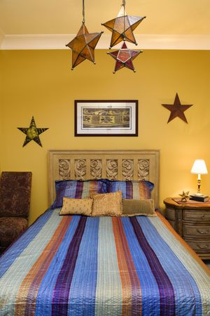 Bed with striped bedspread, decorative stars, and nightstand. Vertical shot. photo