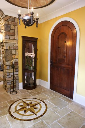 Arched front door and ceramic tile entryway of luxury home with mariner star inset. Vertical shot.