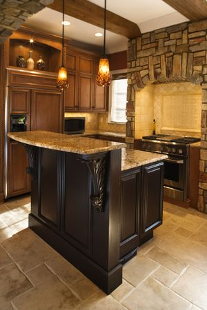 cabinets: Upscale kitchen interior with stone accents and wood beam ceiling. Vertical shot.